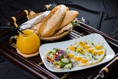 Breakfast wih juice, salat, eggs, bread. Breakfast with eggs, croissant, salad with cucumber, carrots, cabbage and orange juice Royalty Free Stock Photos