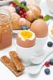 Breakfast with eggs, croissants, fresh berries Stock Image