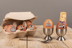 Breakfast eggs with faces. On wooden work top royalty free stock photo