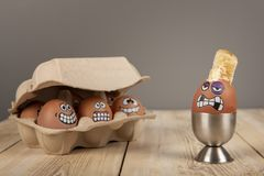 Breakfast eggs with faces. On wooden work top royalty free stock photos