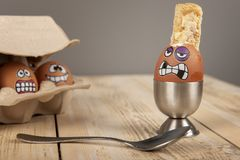 Breakfast eggs with faces. On wooden work top stock photos