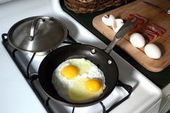 Breakfast - eggs&sausage. Saturday morning breakfast being prepared: fried eggs with sausage on the side royalty free stock images