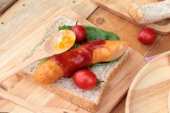 Breakfast with eggs, sausage, bread, salad vegetables and milk. Stock Photos