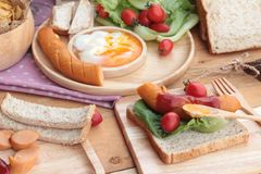 Breakfast with eggs, sausage, bread, salad vegetables and milk. Stock Image