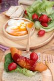 Breakfast with eggs, sausage, bread, salad vegetables and milk. Royalty Free Stock Photos