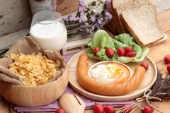 Breakfast with eggs, sausage, bread, salad vegetables and milk. Royalty Free Stock Image