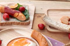Breakfast with eggs, sausage, bread, salad vegetables and milk. Stock Photography