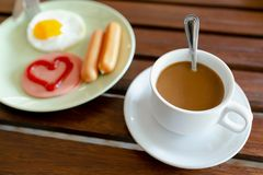 Breakfast, eggs, sausages, ham and black coffee. stock photo