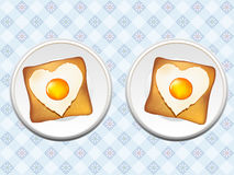 Breakfast of eggs and toast. Two plates of heart-shaped fried eggs on toast, on blue tablecloth Royalty Free Stock Images