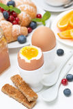 Breakfast with eggs, toasts, croissants, berries Stock Images
