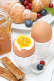 Breakfast with eggs, toasts, croissants, fresh berries, close-up Royalty Free Stock Photo