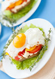 Breakfast, eggs on vegetables and bread Stock Images