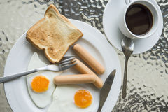Breakfast. English breakfast with fried eggs, sausages, toasts and coffee Royalty Free Stock Images