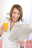 Breakfast - excited woman reading newspaper Royalty Free Stock Image