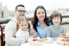 Breakfast of family. Affectionate family sitting by table during breakfast Royalty Free Stock Images