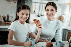 Little girl eating croissants in the kitchen stock image