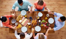Group of people at table praying before meal. Breakfast, family and religious concept - group of people with food sitting at table and praying before meal Royalty Free Stock Images