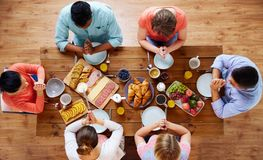 Group of people at table praying before meal. Breakfast, family and religious concept - group of people with food sitting at table and praying before meal Stock Image