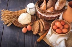 Breakfast from farm products: eggs, milk, bread on a wooden table. Royalty Free Stock Photos