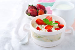 Breakfast with farmer cottage cheese, strawberries and mint. On white background Royalty Free Stock Image