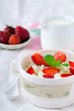 Breakfast with farmer cottage cheese, strawberries and mint. On white background Stock Photography