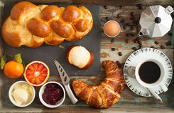 Breakfast Flat Lay. Of freshly baked bread, croissant, pretzel roll along with fruit, boiled egg and coffee. All served on a rustic wooden tray table Royalty Free Stock Image
