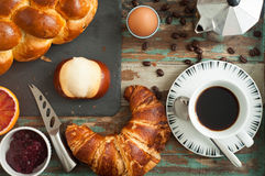 Breakfast flat lay. Of freshly baked bread, croissant, pretzel roll along with fruit, boiled egg and coffee. All served on a rustic wooden tray table Stock Image