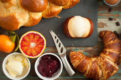 Breakfast flat lay. Of freshly baked bread, croissant, pretzel roll along with fruit, boiled egg and coffee. All served on a rustic wooden tray table Royalty Free Stock Photos