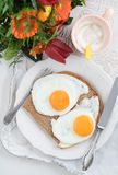 Breakfast with flowers. Breakfast with fried eggs, cappuccino and a bouquet of flowers on a tray Stock Photo