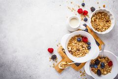Breakfast food background. Granola with milk and berries on white table. Breakfast food background. Granola with milk and berries on a white table, top view royalty free stock photography