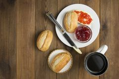 Breakfast food with coffee. Fresh buns with butter and jam on wooden background. Top view. Copy space. royalty free stock image