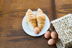 Croissants and brown eggs with basket from above stock photo