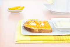 Breakfast. French toast, marmalade, butter, lemon. Breakfast. French toast with spread bitter orange marmalade or jam with candied peel, butter curls, lemon, a Stock Photo