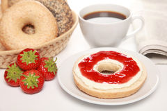 Breakfast with fresh bagels. Served with cream cheese, strawberry marmalade, coffee and a newspaper royalty free stock image