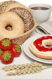 Breakfast with fresh bagels. Served with cream cheese, strawberry marmalade, coffee and a newspaper royalty free stock photography