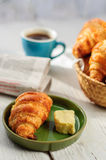 Breakfast with fresh baked croissants, butter and coffee, newspa Royalty Free Stock Photo