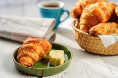 Breakfast with fresh baked croissants, butter and coffee, newspa Stock Images