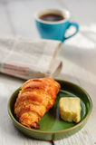 Breakfast with fresh baked croissants, butter and coffee, newspa Stock Photography