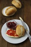 Breakfast with fresh buns and butter, strawbery jam on wooden background. Vertical image. stock photos