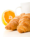 Breakfast of fresh croissants, coffee and orange over white back Royalty Free Stock Images