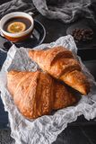 Breakfast with fresh french chocolate croissants on paper over dark background with napkin and cup of tea. Dessert. Puff pastries, top view royalty free stock photography
