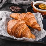 Breakfast with fresh french chocolate croissants on paper over dark background with napkin and cup of tea. Dessert, puff pastries. Closeup stock photo