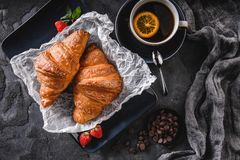 Breakfast with fresh french chocolate croissants on paper over dark background with napkin and cup of tea. Dessert, puff pastries, top view stock images