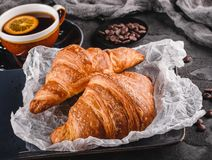 Breakfast with fresh french chocolate croissants on paper over dark background with napkin and cup of tea. Dessert, puff pastries. Closeup royalty free stock photos