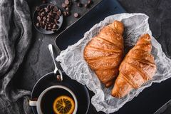 Breakfast with fresh french chocolate croissants on paper over dark background with napkin and cup of tea. Dessert. Puff pastries, top view stock image
