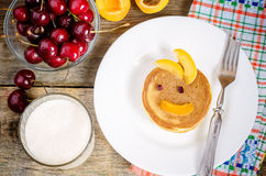 Breakfast with fresh pancakes with cherries and apricots for kid Stock Image