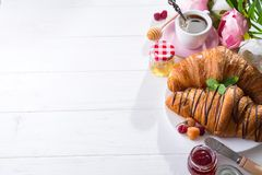 Breakfast freshly baked croissant decorated with jam and chocolate, flowers on wooden table in a kitchen with copy space. Breakfast freshly baked croissant royalty free stock image