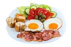 Breakfast fried egg fresh vegetables fried bacon and olives on a white plate  royalty free stock photo