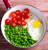 Breakfast with fried egg, green peas and cherry tomatoes Stock Photos