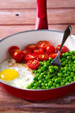 Breakfast with fried egg, green peas and cherry tomatoes Stock Image